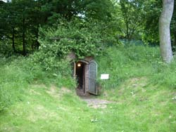 view of the ice house entrance set into a grass covered mound