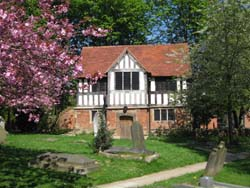 Saint Nicolas Place in its location amongst the trees by Kings Norton Churchyard