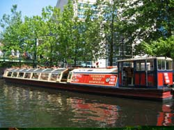 trip boat on a tree lined section of canal in summer