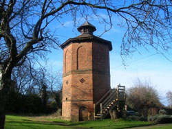 exterior view of the dovecote amongst the trees in the grounds of the hall